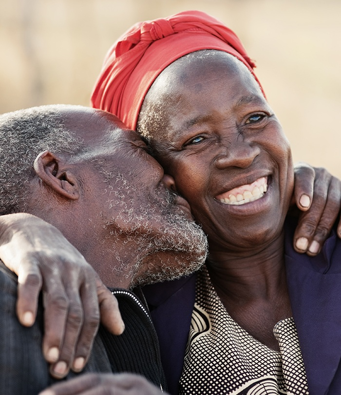 Older man and woman laughing together after replacing missing teeth