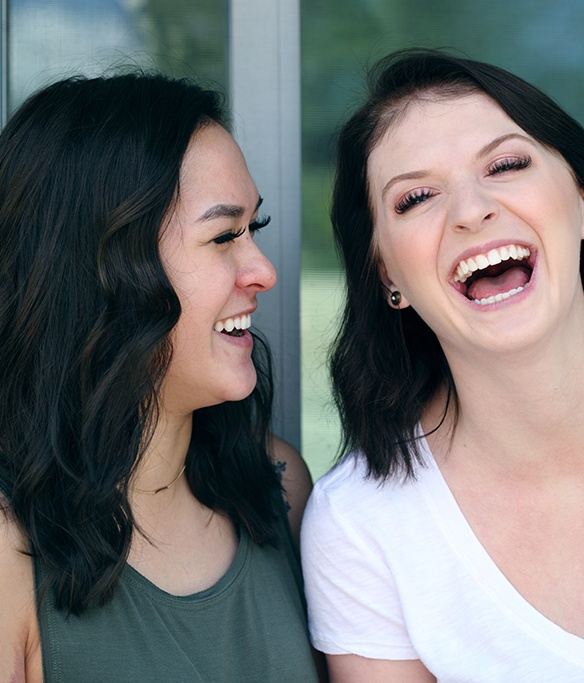Two women laughing together after one visit dental restorations
